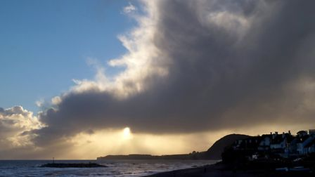 The sun shines through some eye-catching cloud formations off the beach. Picture: Eve Mathews.