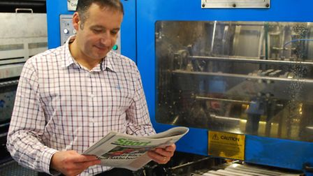 Print centre director Clive Want holding a newspaper hot off the press