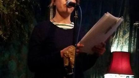 Sarah Acton performing her poetry at an open mic night.
