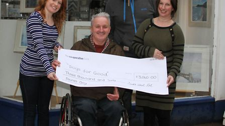 Lynsey and Graham Pickwell with Hannah Twine present a cheque to Phil Day and his dog Noah for Dogs