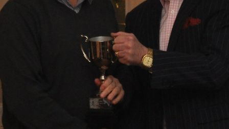 Tom Gooding receives the D Division East champions trophy from Devon League chairman Stuart Munday.
