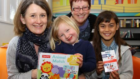 Carol Pentecost from Sidmouth library presents competition winners, Megan with her mum Catherine, an