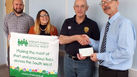 Sidmouth RFC secretary Terry OBrien hands over a cheque for 470 in favour of Children's Hospice Sout