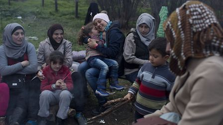 Stranded in the northern Greek border station of Idomeni, for 15 days Syrian refugees sit next to a