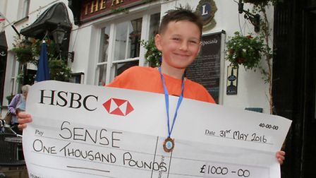 Ben Fisher with his cheque to SENSE after completing the Exmoor Challenge. Ref shs 22-16TI 1285. Pic