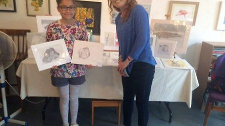 Olivia Middleton, 10, with two of her artworks and teacher Hannah Twine