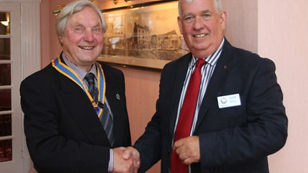 Outgoing Sidmouth Rotary president Ron Galling (left) congratulates the new president Keith Walton t