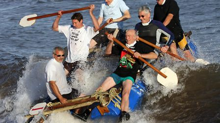 Sidmouth Regatta raft race on Saturday evening. The team from All Saints church catch a wave and sur