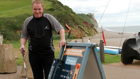 Adrian Wilkes with the new clean-up board at Branscombe beach. Ref shb 30-16TI 5094. Picture: Terry