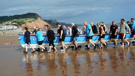 At the end of the day Sidmouth club members, aided by many visiting rowers, carry their boat, Keith