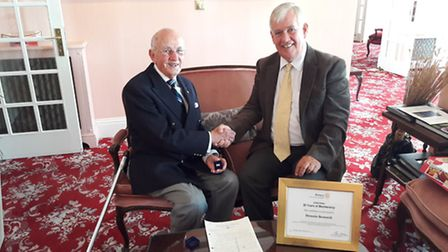Dennis Bennett receives a certificate and badge to recognise 50 years of service in Rotary.