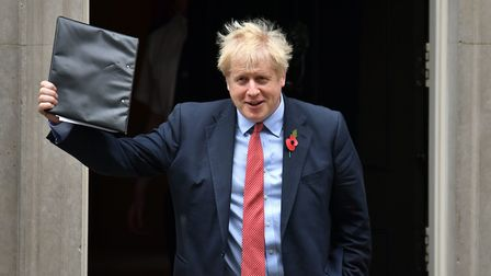 Boris Johnson waves a folder as he leaves 10 Downing Street. Photograph: Dominic Lipinski/PA Wire.