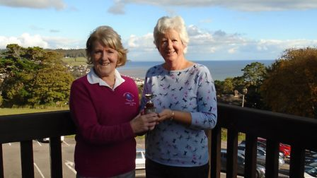 Lady Captain Angela Coles presents the trophy to secretary Sue Langdon after the annula meeting betw