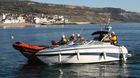 Lyme lifeboat tows the fire cheif's boat to the safety of the harbour