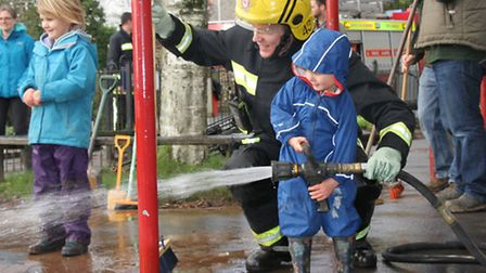 Youngsters helped Sidmouth firefighters hosing down the playground at Tipton primary school. Ref sho