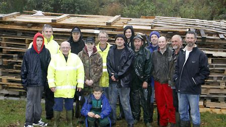 Roger Davey and volunteers standing in front of the bonfire for the Sidbury fireworks display at Sid