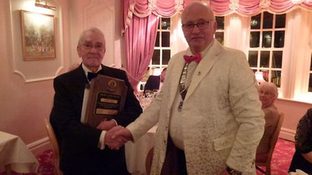 Lion Dennis James receiving the MJF Award from district governor Fred Broom