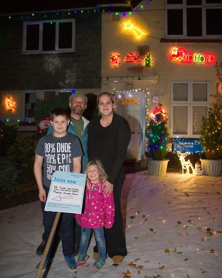 Lawrence Morrell and Becky Hillier with Lewi and Phoenix in front of their christmas house lights. R
