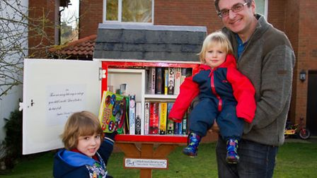 Stuart Ireland and his sons James and Harlan with their community library. shs 01-17TI 4885. Picture