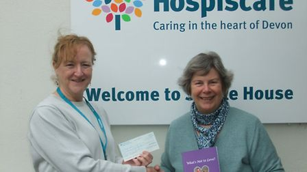 Janet Beardsall (holding her book) presents a cheque to Karen Turner of Hospiscare