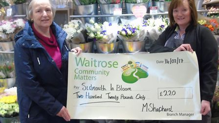 Sidmouth in Bloom's Cheryl Allen claiming the cheque from Julie Marish of Waitrose.