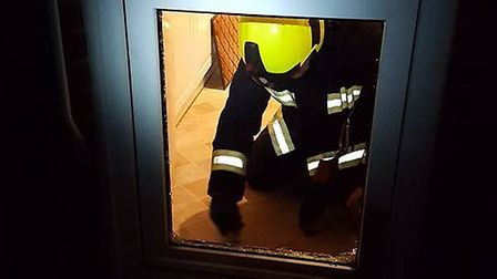 A fire fighter breaks a glass pane after paramedics were unable to gain entry to a Sidmouth property