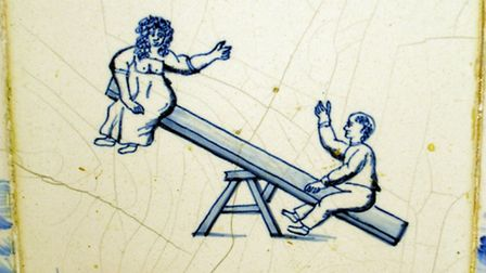A tile at Knowle showing children on a see-saw