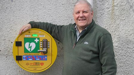 Campaigner John Rush with the new defibrillator outside Sidbury Village Hall.