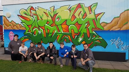 Graffiti artist Sam Giles (centre) with youth workers and center users.