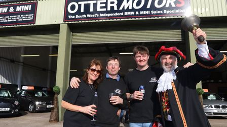 Town Crier Laurie Palmer joined Adrian & Sarah Cook and their son Tom at Otter Motors. Ref: Archant7