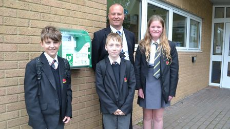 Principal James Ingham-Hill and pupils with the new defibrillator. Sidmouth College is supporting th