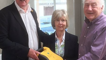 Councillor Stuart Hughes presenting a defibrillator to Twyford House trustees Frances Newth and Phil