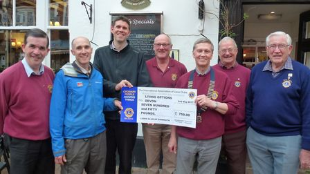 Sidmouth Lions Club president Alan Shoesmith presenting the cheque for the countryside mobility proj