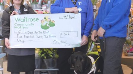 Guide Dogs local organizer Kevin Tierney with guide dog owner John Evans and his dog, Johnny, receiv