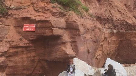 Dave Collingwood saw two young girls sitting underneath a sign that read danger unstable cliff rock