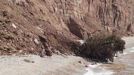 A young man sits at the foot of a recent cliff fall accompanied by a small drone. Picture: Eve Mathe