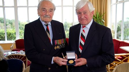 War veteran Raymond Savage receiving a medal from Bob Allen. Picture: Terry Ife