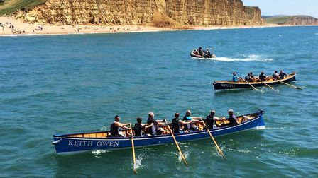 At the foot of West Bay's famous cliffs, the Sidmouth men's A crew return to harbour after their rac