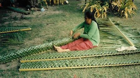 A woman making a feast tray in Tonga which Harold and Judy later got to each from.