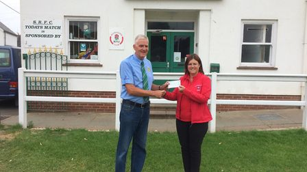 Lester Wilmington, chairman of Sidmouth Rugby Club, presents a cheque to Devon Air Ambulance.