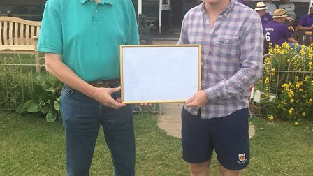 Dave Watkins receiving a framed score card from his recent century scored in the club's third XI.