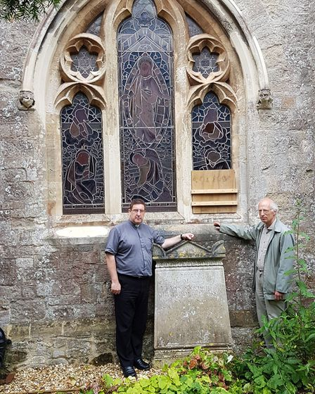The Reverend Canon Dr Philip Bourne and churchwarden Professor Brian Golding by the damaged stained
