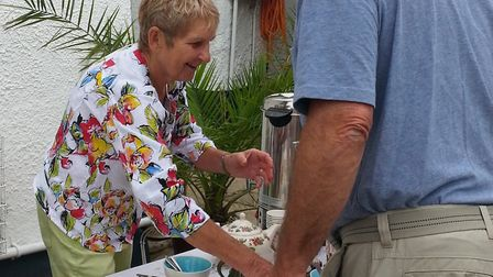 Jackie Baum serving a guest at her fundraising garden party for Harpford Hall