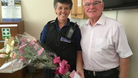 Mayor Glyn Dobson presents Maria Clapp with flowers, cards and a voucher to thank her for her servic