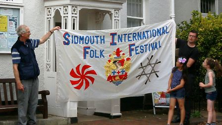 Sidmouth Museum curator Nigel Hyman receiving the FolkWeek banner from filmmaker Paul Tully. Sidmout