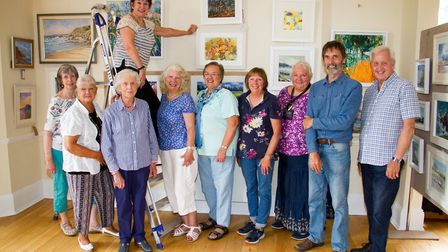 Lynda Kettle, chairman of Sidmouth Society Of Artists with members at their exhibition hanging in Ke