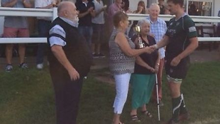 The David Turner Cup being presented to Sidmouth captain Ollie Pyne by David's mother Jean. In atten