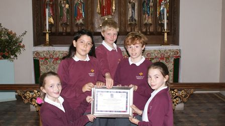 Pupils at Tipton St John Primary School collect their outstanding certificate in a recent SIAM inspe