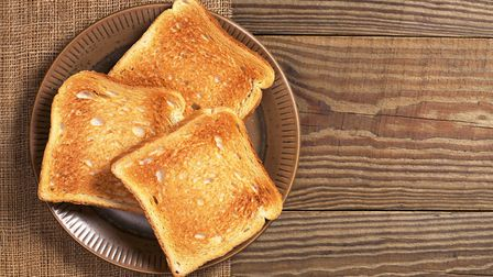 Slices of toasted bread on plate on wooden table. Thinkstock image.