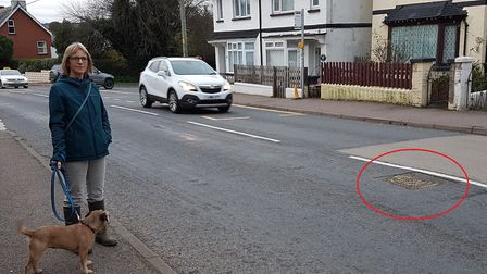 Councillor Val Ranger with the problem drain cover in High Street, Newton Poppleford